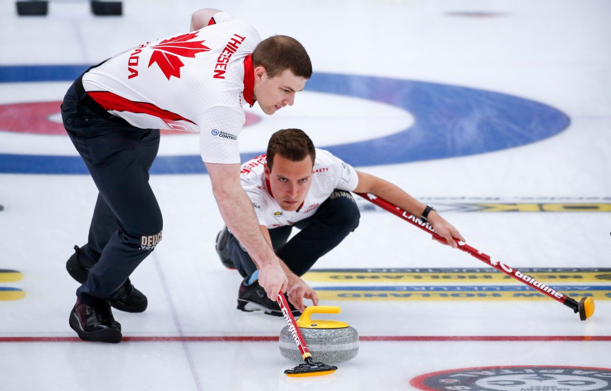 Team Canada skip Brendan Bottcher, right, makes a shot  as second Brad Thiessen sweeps against Norway at the Men's World Curling Championships in Calgary, Alta., Thursday, April 8, 2021.