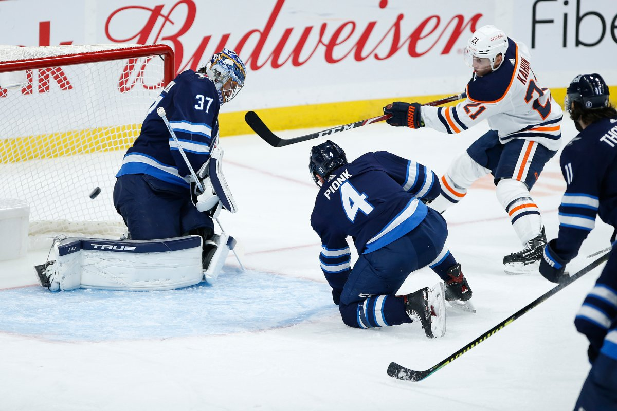 Winnipeg Jets goaltender Connor Hellebuyck (37) saves the shot from Edmonton Oilers' Dominik Kahun (21) as Neal Pionk (4) defends during second period NHL action in Winnipeg on Saturday, April 17, 2021.