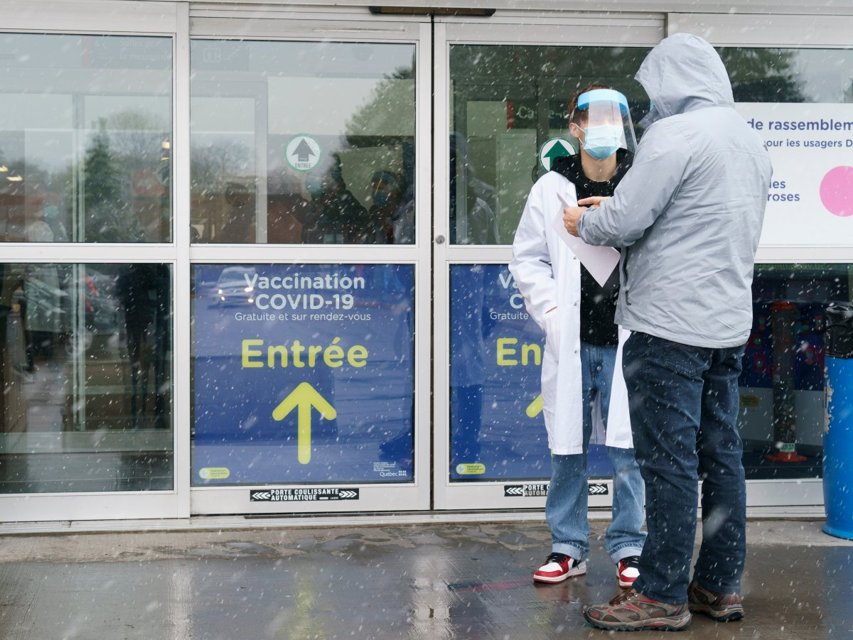 A man is screened before entering a COVID-19 vaccination clinic in Montreal, on Wednesday, April 21, 2021.