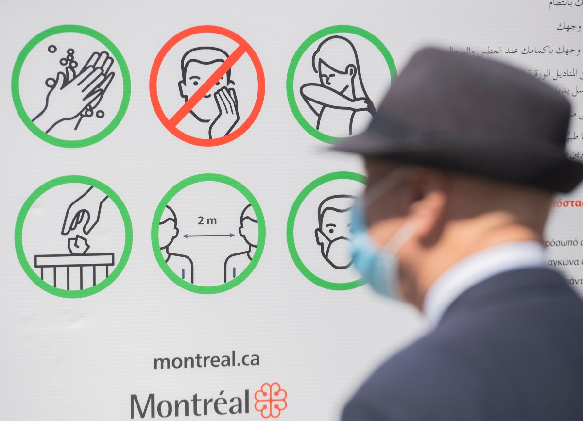 A man wears a face mask as he looks at a sign illustration COVID-19 preventative measures in Montreal, Saturday, April 24, 2021.