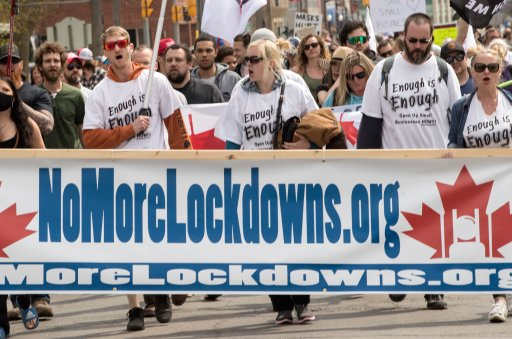 Demonstrators march at a protest against government measures to curb the spread of COVID-19, in Peterborough, Ont., on April 24, 2021. THE CANADIAN PRESS/Fred Thornhill