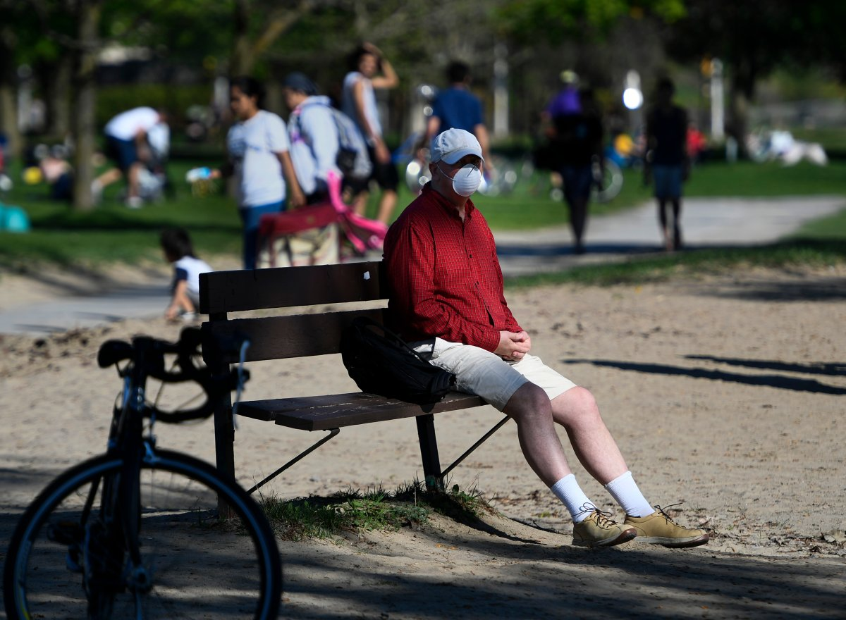 A person rests on a bench at Mooney's Bay Beach in Ottawa, on Saturday, May 23, 2020, in the midst of the COVID-19 pandemic. City staff might implement stricter closing times on the site and other parks in the city this summer.