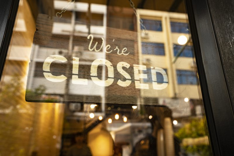 File: Closed sign hanging in business window by a string.