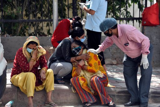 Grieving relatives and family members of COVID-19 victims wait outside Maulana Azad Medical College mortuary to collect their bodies, on April 25, 2021, in New Delhi, India.