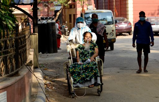 A Covid-19 patient on a wheel chair goes for a medical test inside a government hospital in Kolkata, India, 27 April, 2021.