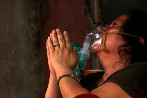 A woman suffering from a breathing difficulty due to the coronavirus disease (COVID-19), prays while receiving free oxygen support outside a Gurudwara (Sikh temple) in Ghaziabad, India, on April 28, 2021.