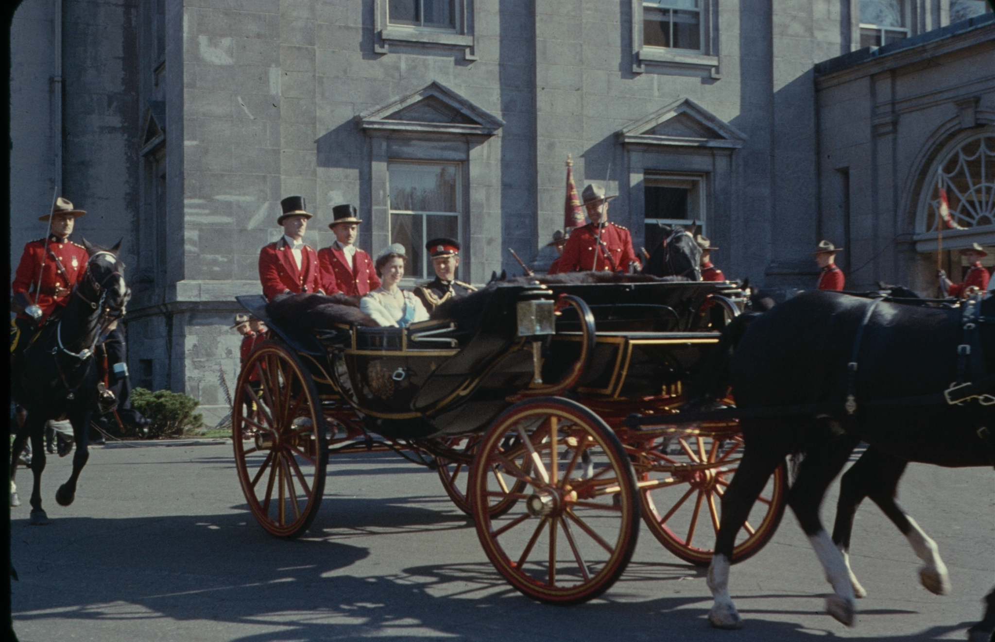 Queen Elizabeth II and Prince Philip riding in a carriage together with the royal guards, Ontario, Canada, October 1957.