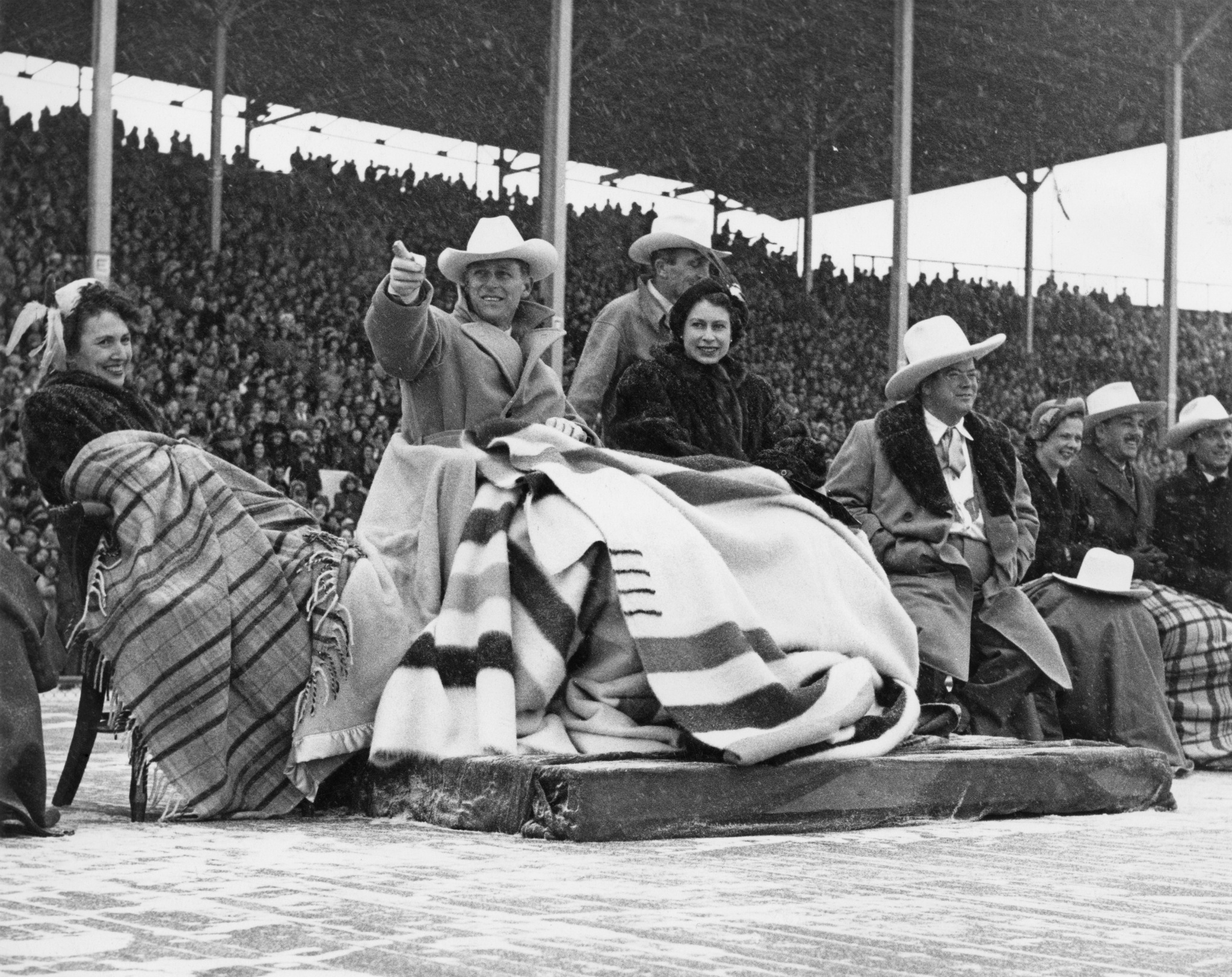 Princess Elizabeth and Prince Philip brave a snowstorm to watch a stampede at Calgary exhibition grounds, Canada, Oct. 24, 1951. Next to the Princess is Donald Hugh Mackay, Mayor of Calgary. The Princess is wearing a mink fur coat, a wedding present from Canada.