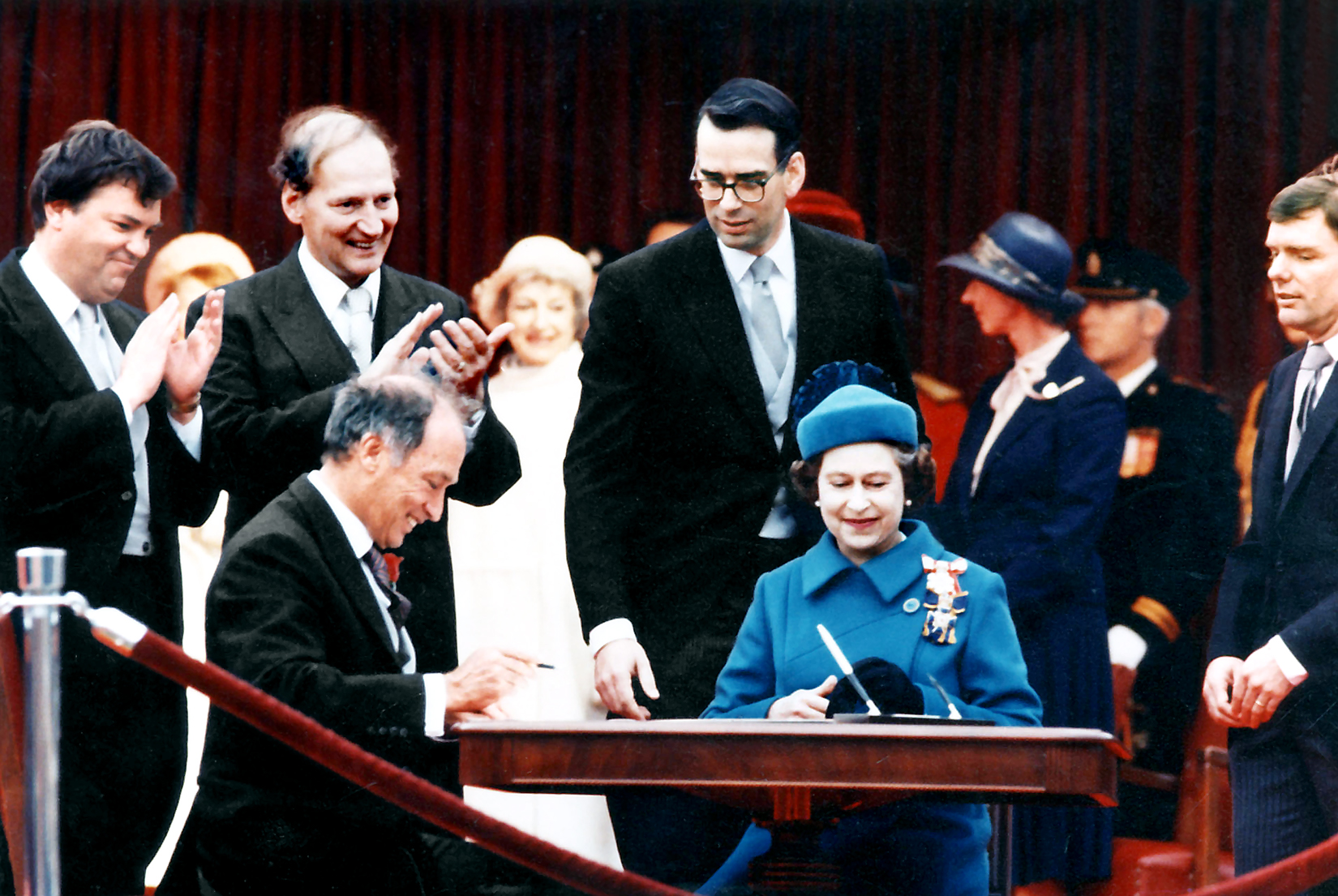 Prime Minister Trudeau and the Queen prepare to sign the Constitution proclamation as Consumer Affairs Minister Ouellet (left), Secretary of State Regan and Privy Council Clerk Pitfield look on.