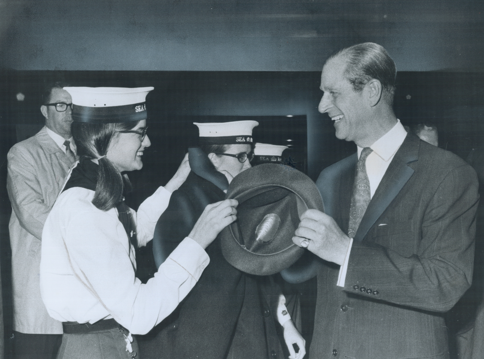 It may look like a tug-of-war; but it's just Dianne Murray returning Prince Philip's hat to him after a rally of Venturer Scouts in the Scarborough Centennial Arena. Philip presented certificates to teenagers who have completed requirments for the Duke of Edinburgh Award; and looked at displays of activities.