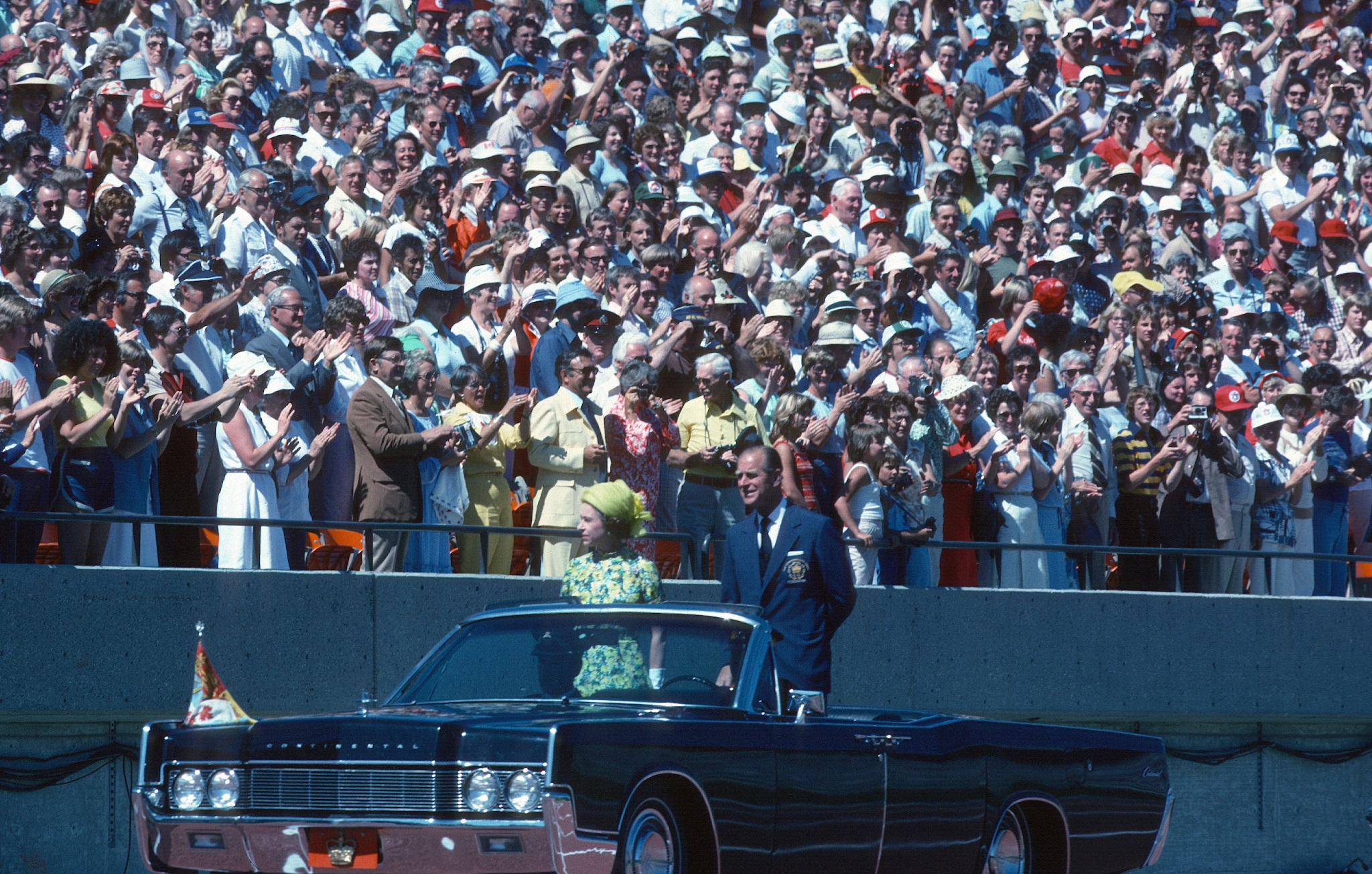 Queen Elizabeth ll and Prince Philip, Duke of Edinburgh ride in an open car past spectators in the stands as they arrive to open the Commonwealth Games on Aug. 3, 1978, in Edmonton, Canada.