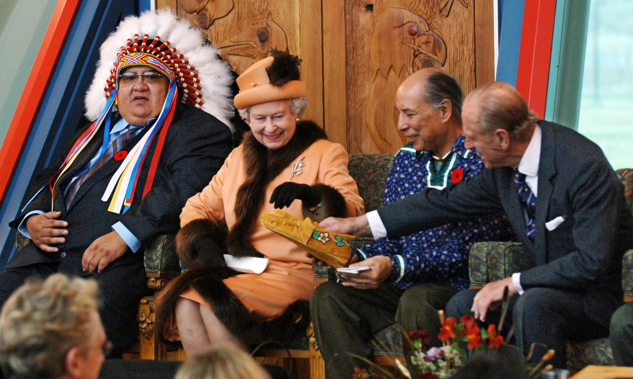 Queen Elizabeth II is shown some moccasins by the Duke of Edinburgh after he was presented with them during their visit to the First Nations University in Regina.