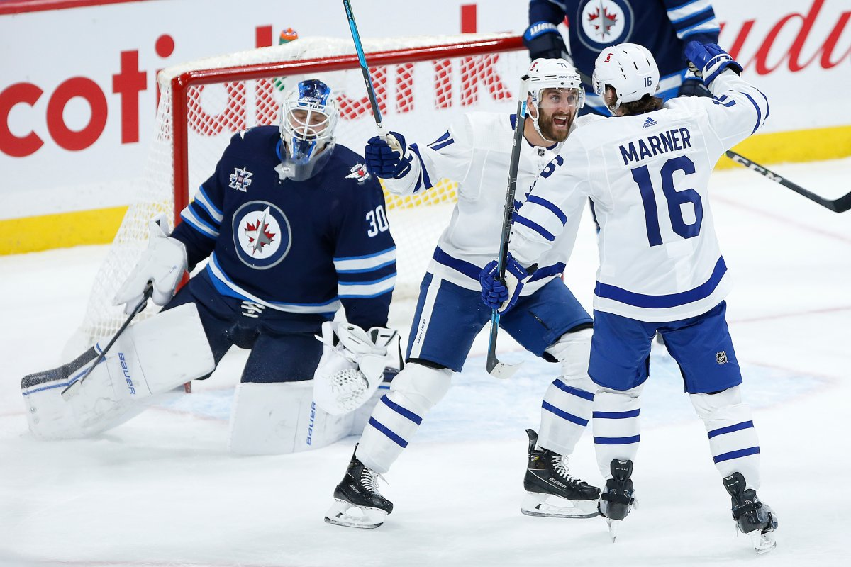 Toronto Maple Leafs' Nick Foligno (71) and Mitchell Marner (16) celebrate Marner's goal on Winnipeg Jets goaltender Laurent Brossoit (30) during second period NHL action in Winnipeg on Thursday, April 22, 2021.