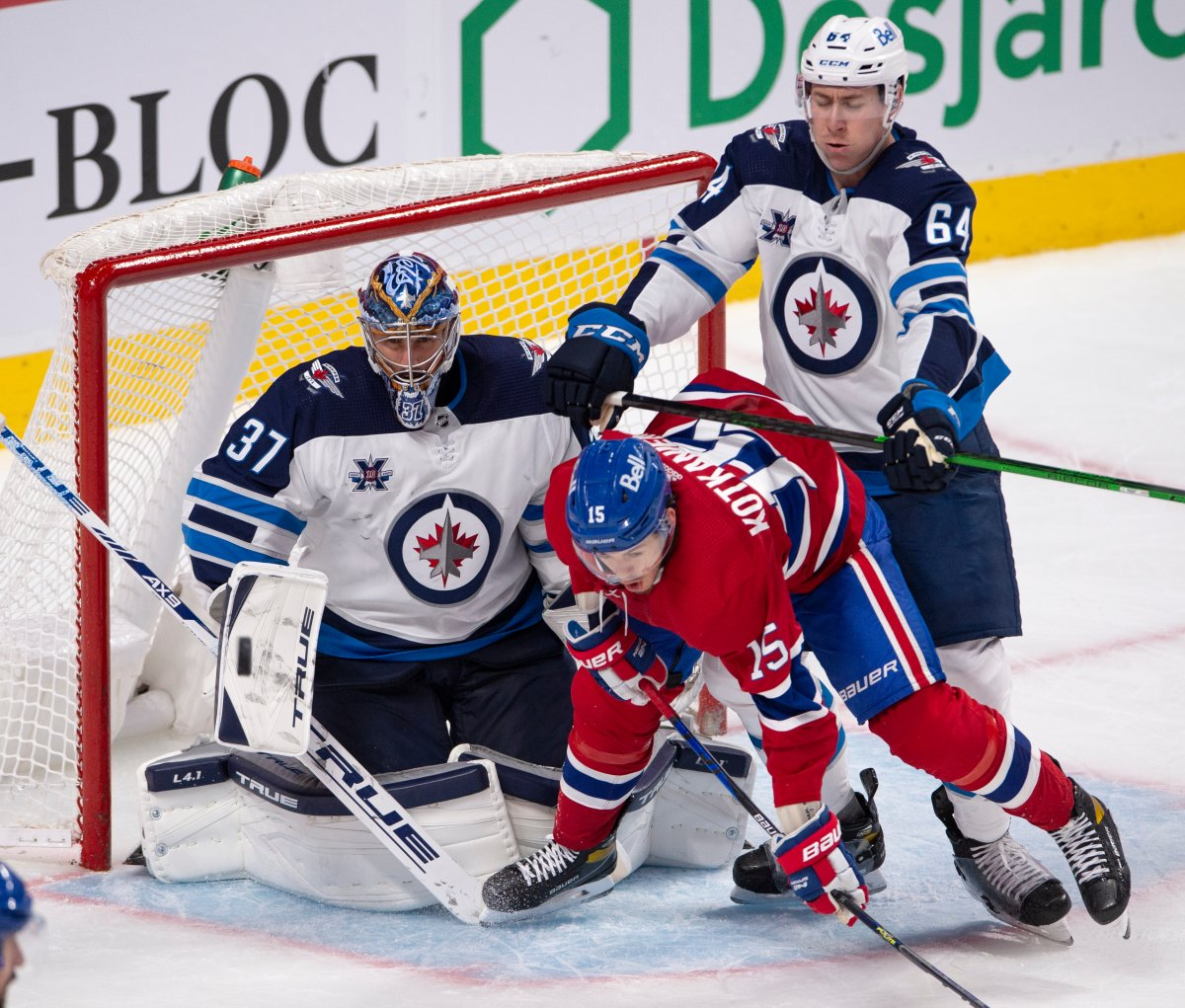 Winnipeg Jets' Logan Stanley (64) crosschecks Montreal Canadiens' Jesperi Kotkaniemi (15) in front of Jets goaltender Connor Hellebuyck (37) during third period NHL hockey action Thursday, April 8, 2021 in Montreal.