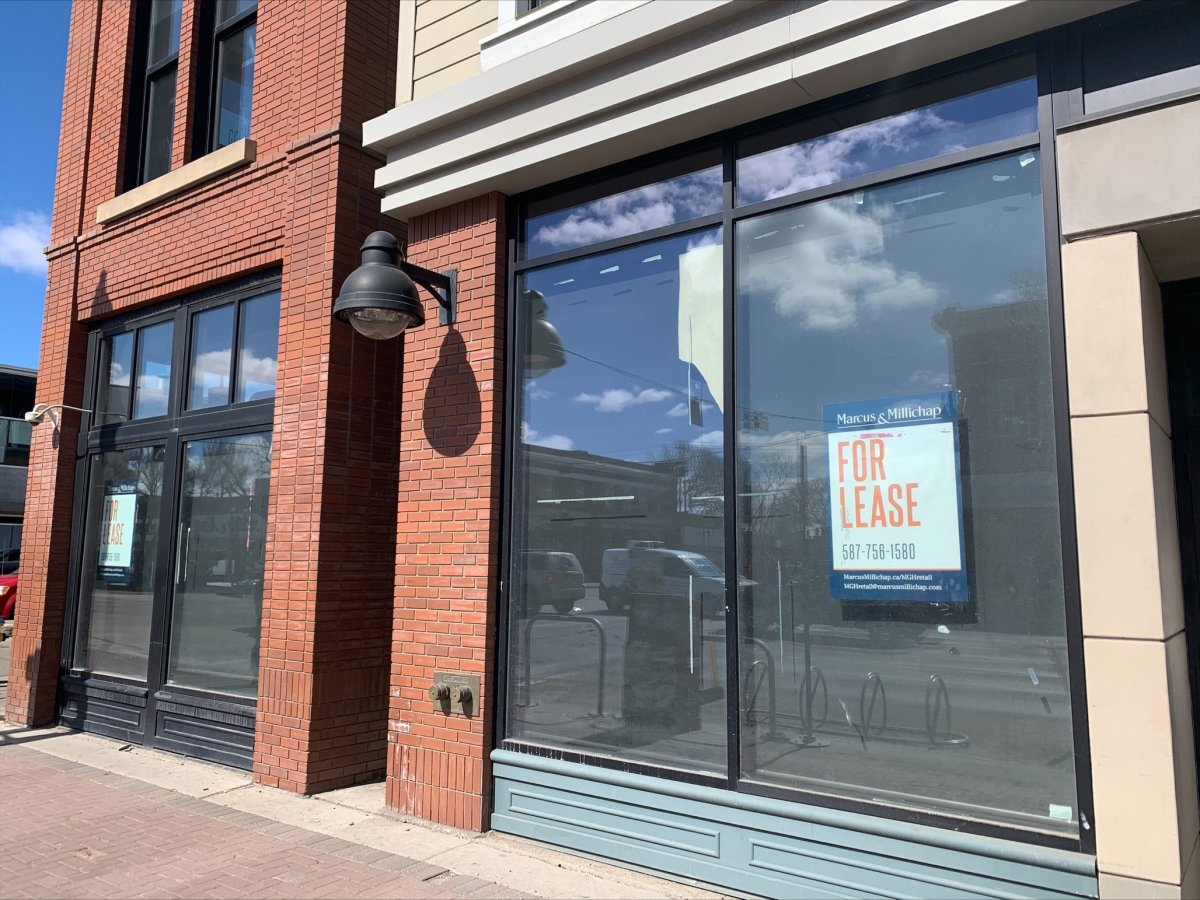 An empty storefront shows for lease signs in the window on Whyte Avenue and 104 Street.