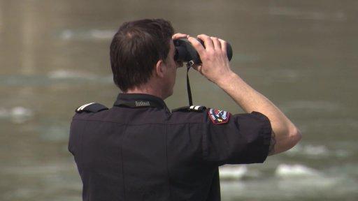 An Edmonton firefighter searching the North Saskatchewan River with binoculars in Edmonton, Alta. on Tuesday, April 6, 2021.