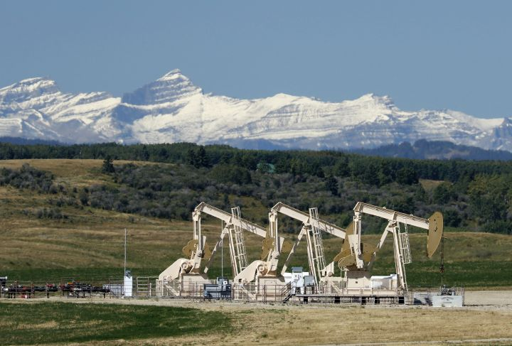 Oilfield pumpjacks, belonging to Whitecap Resources, work producing crude near Calgary, Alberta on Sept. 9, 2020. The Rocky Mountains are visible in the distance.