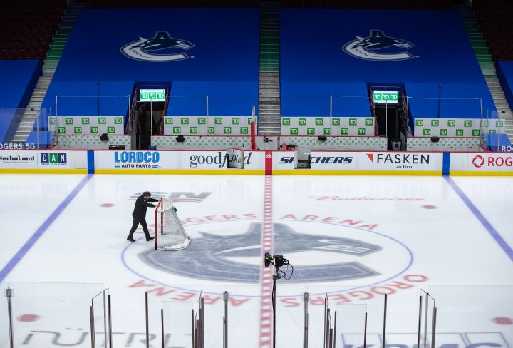 An arena worker removes the net from the ice after the Vancouver Canucks and Calgary Flames NHL hockey game was postponed due to a positive COVID-19 test result, in Vancouver, on Wednesday, March 31, 2021.
