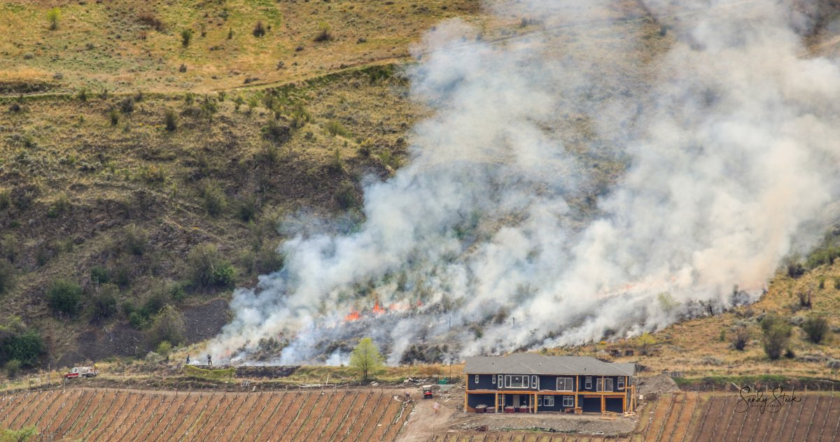 The Oliver Fire Department said Tuesday's grass fire was burning about 100 metres from a residence.