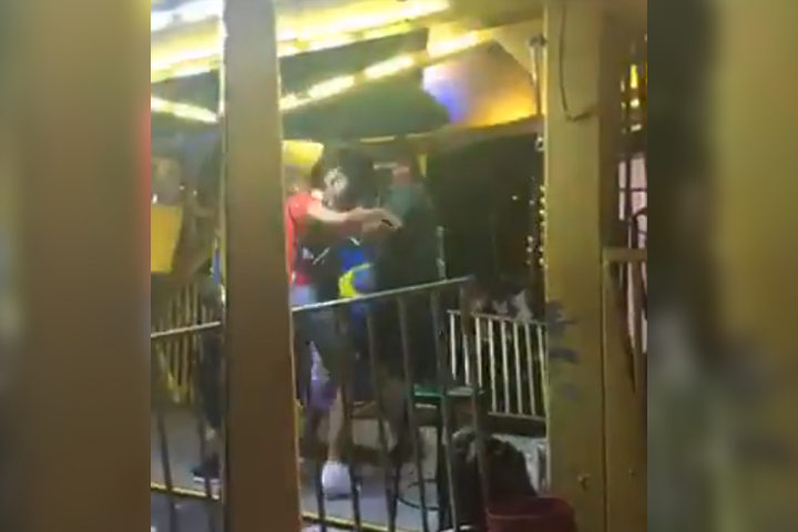 A ferris wheel operator and a woman trade blows during a dispute in Opa Locka, Fla., in this image from a Facebook Live video on April 17, 2021.