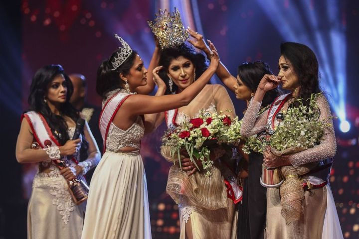 In this photograph taken on April 4, 2021, winner of Mrs. Sri Lanka 2020 Caroline Jurie (2-L) removes the crown of 2021 winner Pushpika de Silva (C) as she is disqualified by the jurie over the accusation of being divorced, at a beauty pageant for married women in Colombo.