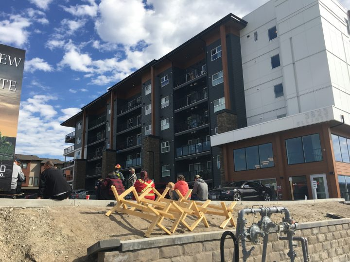 People sit outside an evacuated apartment building in West Kelowna on Sunday morning.