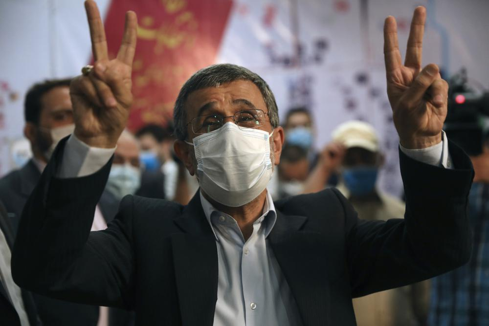 Former President Mahmoud Ahmadinejad flashes victory sign while registering his name as a candidate for the June 18, presidential elections at elections headquarters of the Interior Ministry in Tehran, Iran, Wednesday, May 12, 2021.