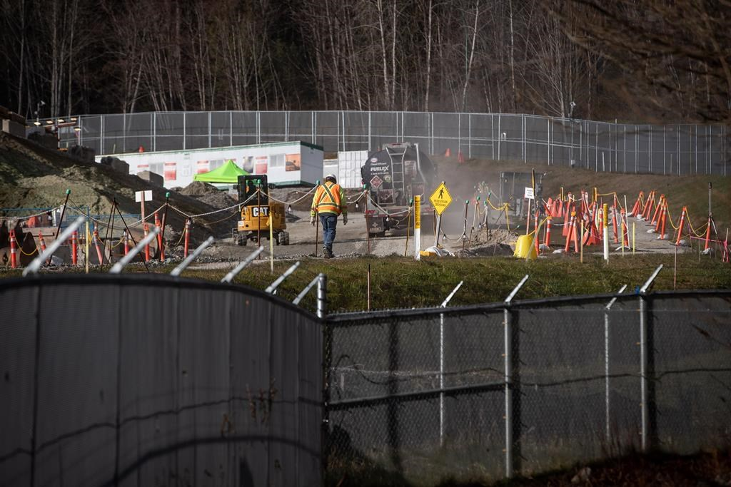 A construction worker walks through the site as work continues on the Trans Mountain Pipeline expansion project at the company's Burnaby Terminal tank farm in Burnaby, B.C., on Wednesday, March 10, 2021. THE CANADIAN PRESS/Darryl Dyck.