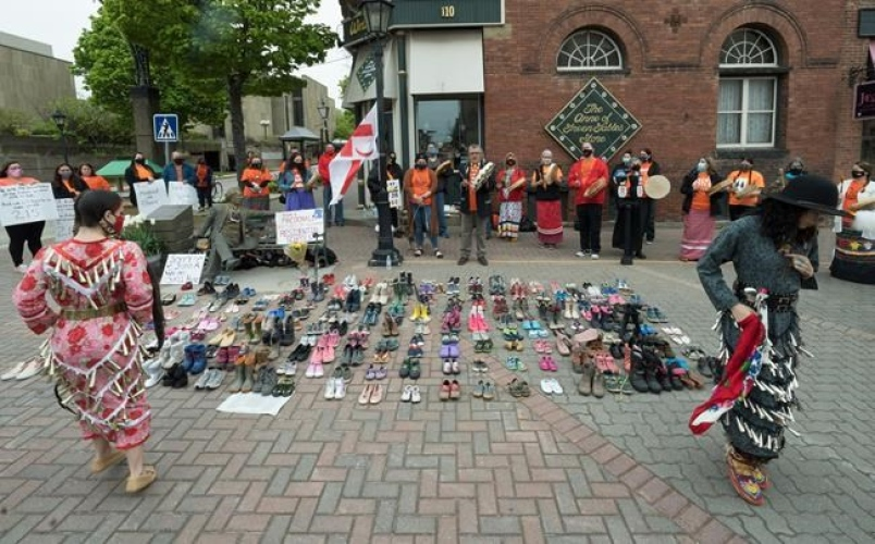Two Indigenous dancers perform around the 215 pairs of children's shoes placed next to a Sir John A. Macdonald statue in Charlottetown on Monday, May 31, 2021, during a ceremony for the remains of 215 children found at the Kamloops Indian Residential School.