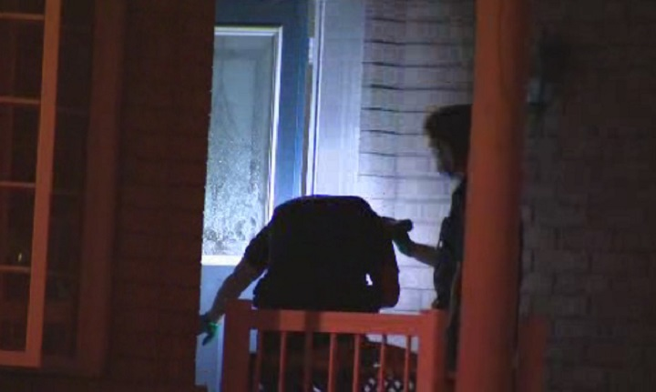 Peel Regional Police officers examine the front door of a home.