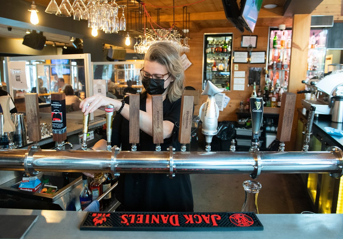 A server pours a beer at a bar and restaurant in Saint-Sauveur, Que., Saturday, December 12, 2020, as the COVID-19 pandemic continues in Canada and around the world.