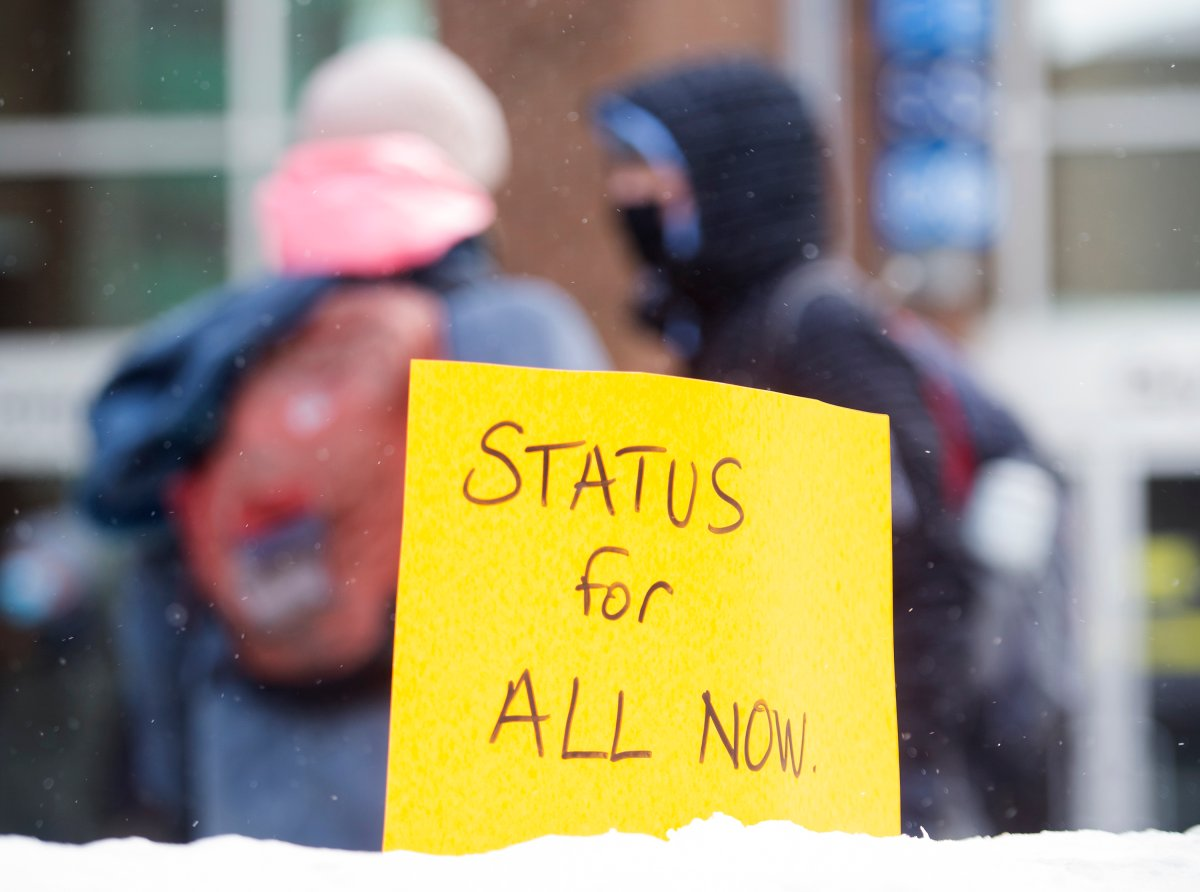 "A sign reading ""Status for All Now"" is shown planted in a snowbank during a protest in Montreal, Saturday, January 30, 2021, to demand status for all workers and to demand dignity for all non status migrants as full human beings as the COVID-19 pandemic continues in Canada and around the world. THE CANADIAN PRESS/Graham Hughes."