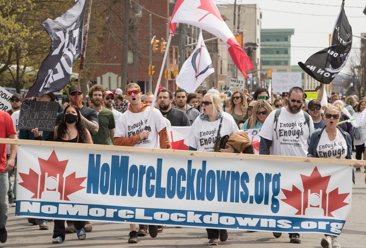 Demonstrators march at a protest against government measures to curb the spread of COVID-19, in Peterborough, Ont., Saturday, April 24, 2021.