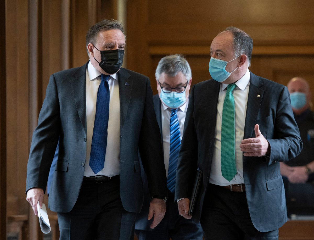Quebec Premier Francois Legault, left, chats with Quebec Health Minister Christian Dube, right, as they walk to a news conference on the COVID-19 pandemic, Tuesday, May 4, 2021 at the legislature in Quebec City. Horacio Arruda, Quebec director of National Public Health follows.