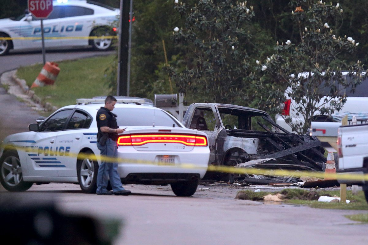 Hattiesburg police surround a burned automobile and a damaged home after a small plane crashed late Tuesday night in Hattiesburg, Miss., Wednesday May 5, 2021.  Emergency officials in Mississippi say multiple people were killed when the small plane crashed into a home. (AP Photo/Chuck Cook).