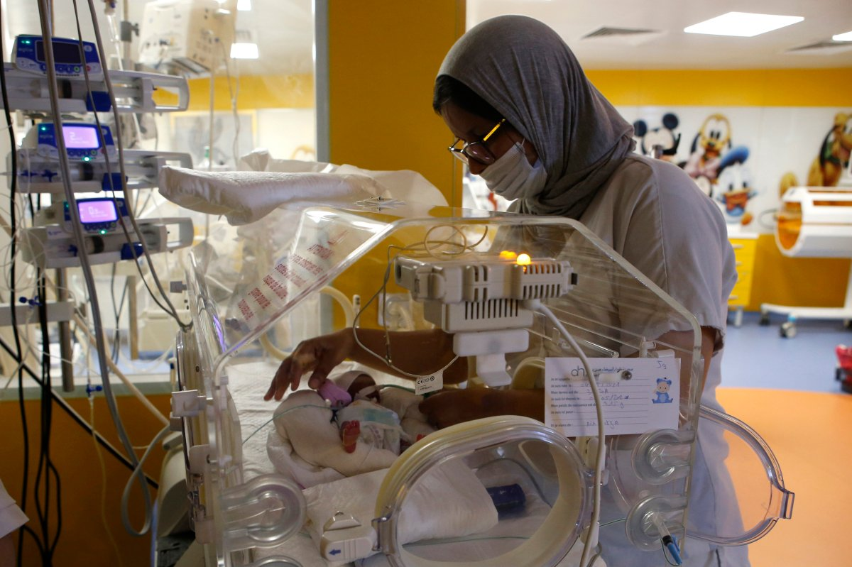 A Moroccan nurse takes care of one of the nine babies protected in an incubator at the maternity ward of the private clinic of Ain Borja in Casablanca, Morocco, Wednesday, May 5, 2021.
