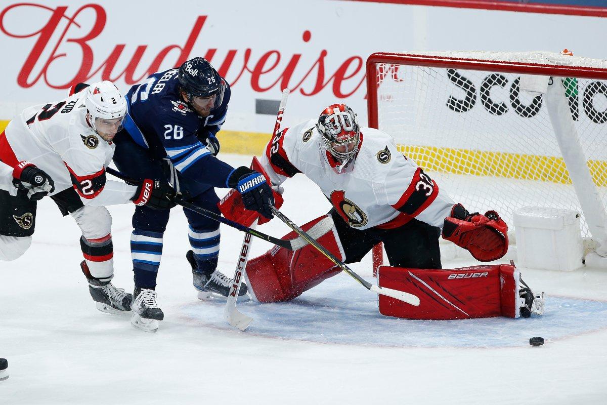 Ottawa Senators goaltender Filip Gustafsson (32) saves the shot by Winnipeg Jets' Blake Wheeler (26) as Artem Zub (2) defends during second period NHL action in Winnipeg on Saturday, May 8, 2021.