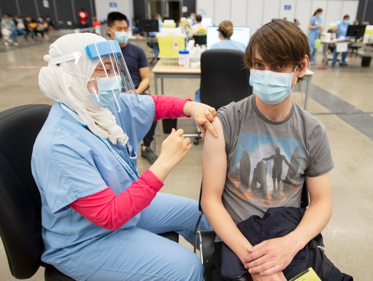 Bertrand Legane, 30, receives a dose of the Pfizer vaccine at a COVID-19 vaccination clinic, Thursday, May 13, 2021  in Montreal.