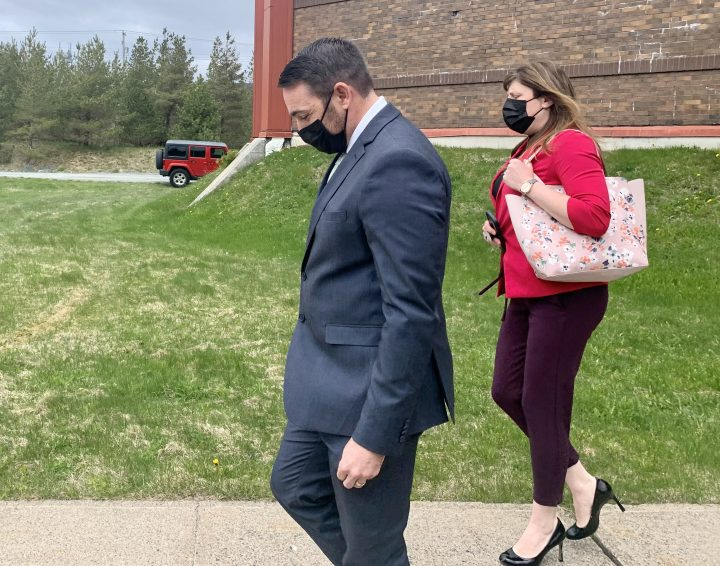 Royal Newfoundland Constabulary Const. Carl Douglas Snelgrove keeps his head down as he leaves court on Thursday, May 13, 2021 in St.John's, after a jury was sequestered to determine whether or not he is guilty of sexually assaulting a 21-year-old woman while on duty in 2014.