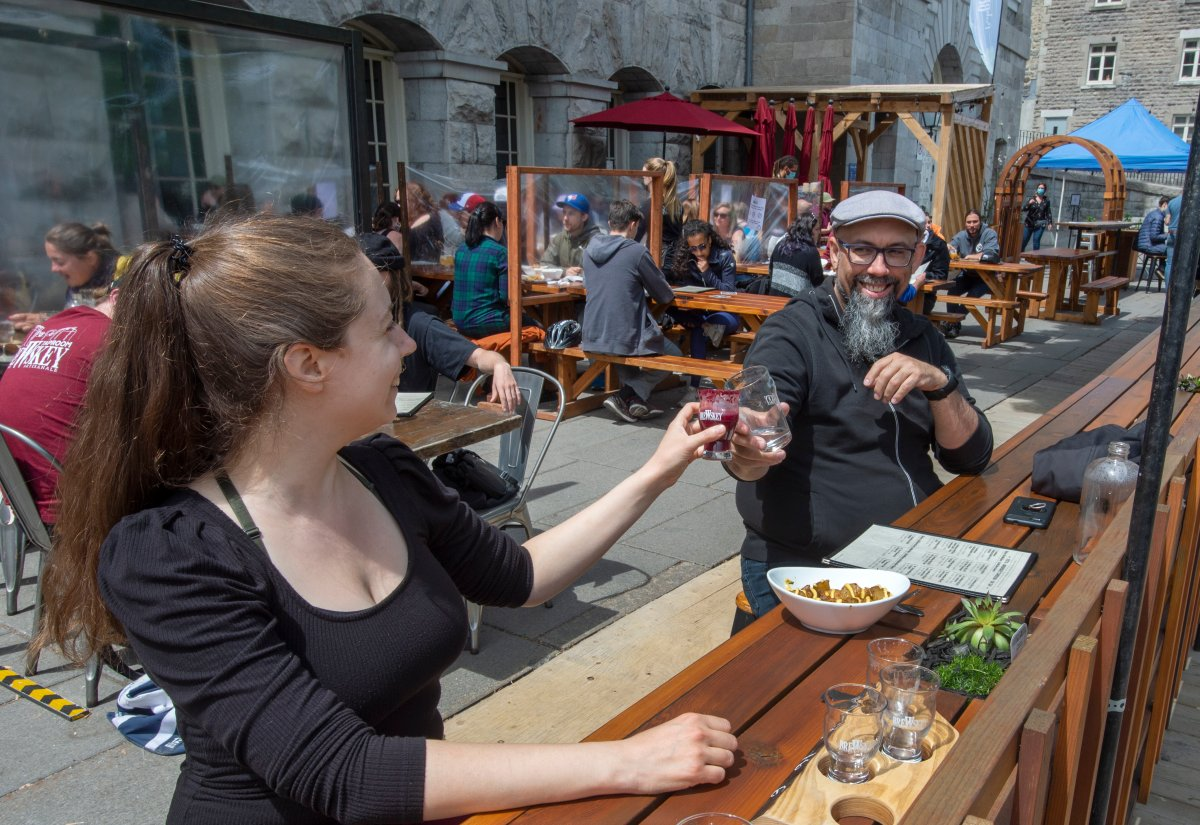 Lawrence L'Oisselle, left, and Eric Deschamps enjoy a restaurant patio as they re-open for the first time since last September in Montreal as Quebec begins easing its COVID-19 restrictions on Friday, May 28, 2021.