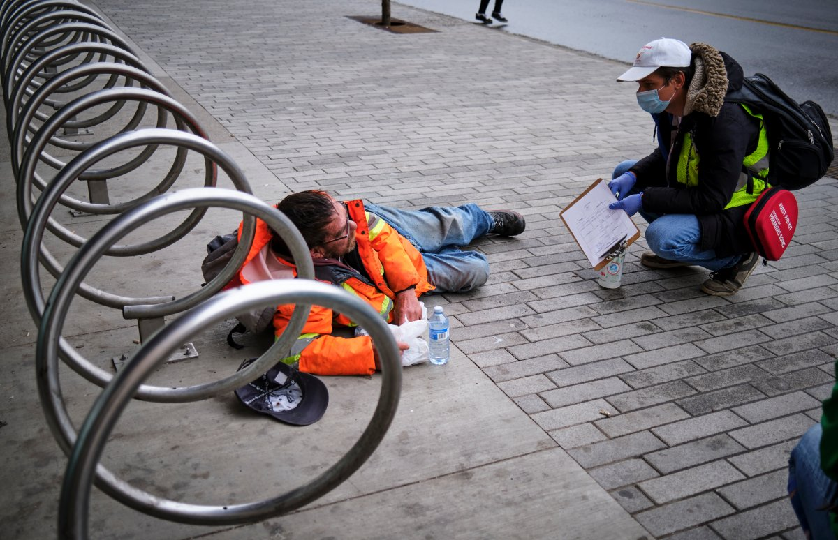 Volunteer Chaz Smith (right) distributes aid to a homeless man in Calgary on Wednesday, May 20, 2020, amid the COVID-19 pandemic.