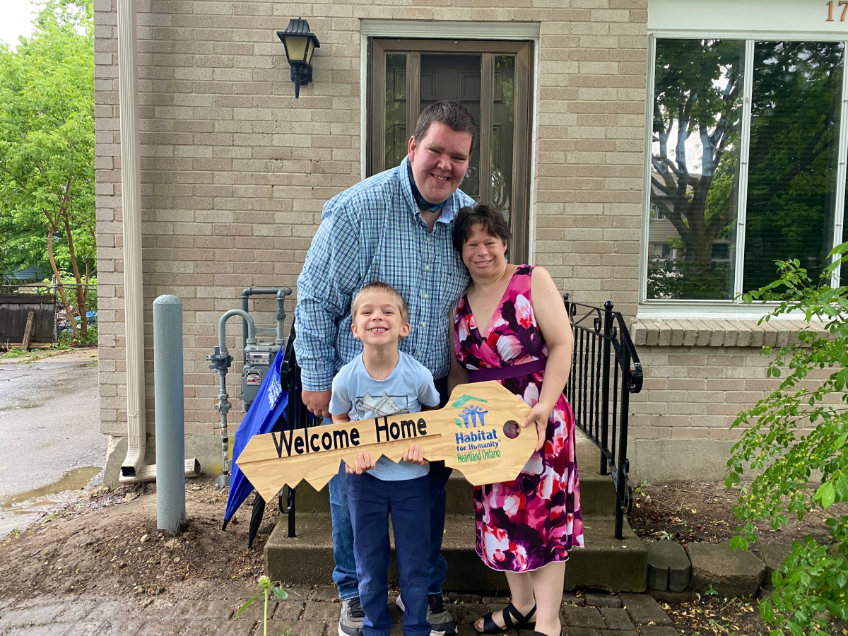 Jamie, Jennifer and their son Christopher stand in front of their new home on Culver Drive ahead of a virtual ceremony on Wednesday.