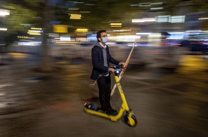 A man wearing a face mask to protect against coronavirus, as he drives his E-scooter in central Frankfurt, Germany, Monday, Oct. 5, 2020.