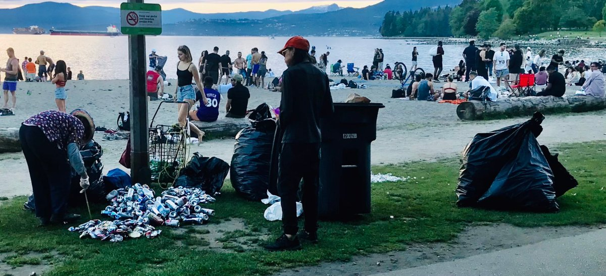 Binners are cleaning up empties at English Bay in Vancouver Sunday after a large crowd of people gathered on the beach to drink and party.