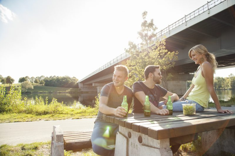 Three young friends drinking beer on riverside picnic table.