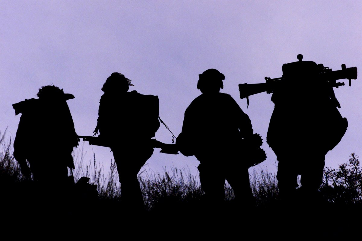 FILE - Canadian infantry soldiers from 3-PPCLI carry battle gear including a shoulder launched rocket as they walk a ridge line March 14, 2002 in the Shahi Kot mountains in Afghanistan.