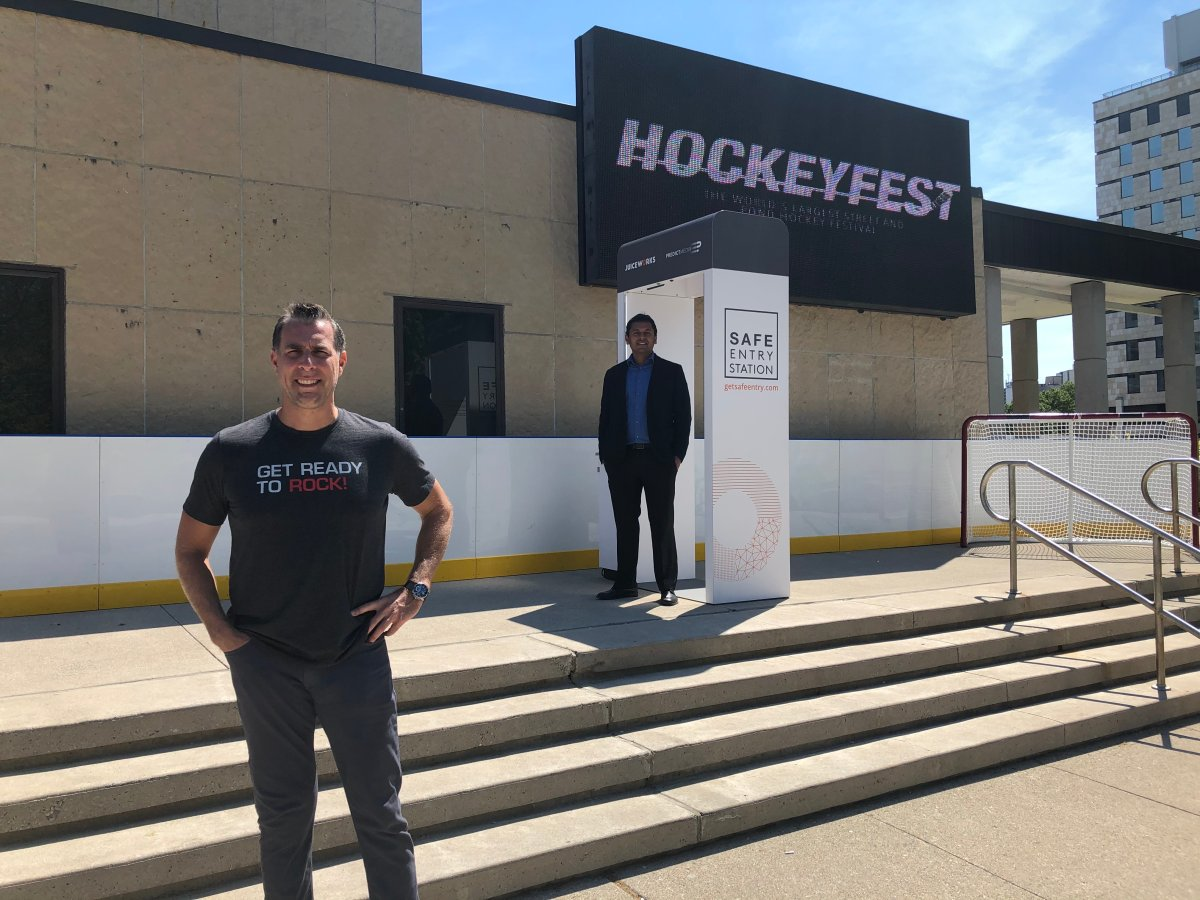 Jones Entertainment Group president Brad Jones (left) and PredictMedix COO Dr. Rahul Kushwah stand by a Safe Entry Station, a screening device that will be deployed at Hockeyfest and Rock the Park.