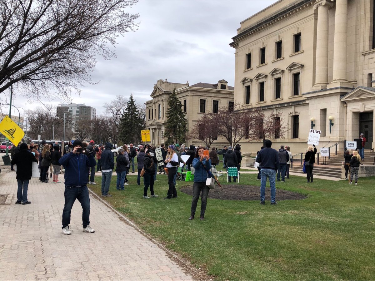Protestors gather outside the provincial court building in Winnipeg Monday for an anti-restrictions rally.