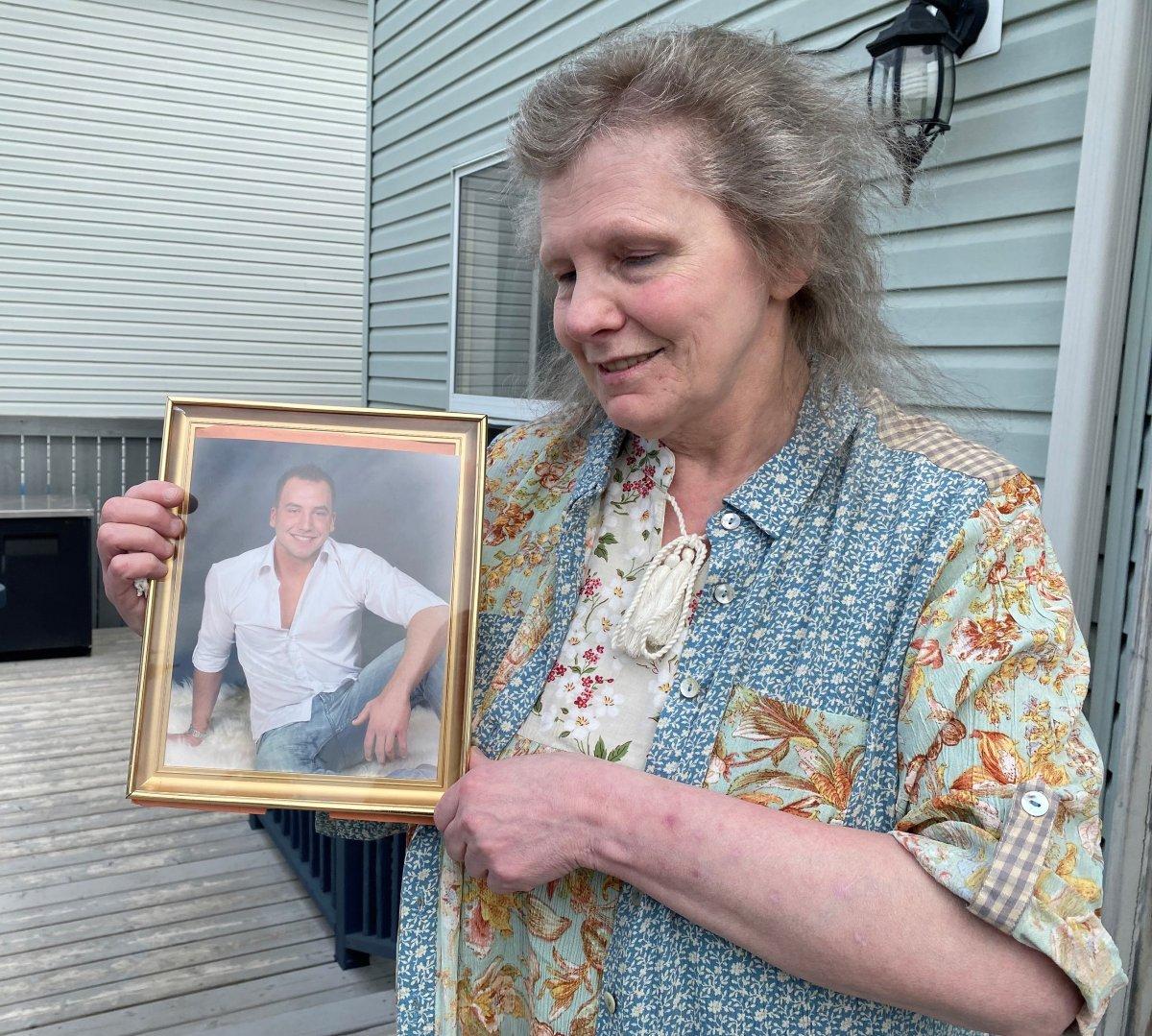 Maryann Reinke holds a photograph of her son, Gavin Zima, on May 17 2021.