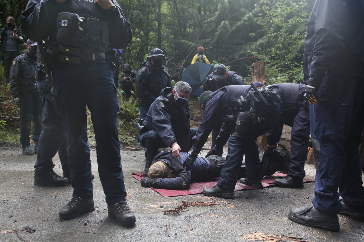 RCMP officers arrest a man during an anti-logging protest in Caycuse, B.C. on Tuesday, May 18, 2021.